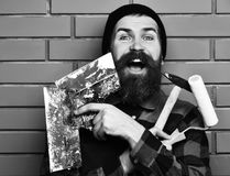 Bearded builder man holding various building tools with happy face. Bearded builder man, long beard, brutal caucasian hipster with moustache in uniform holding stock photo