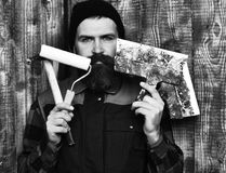 Bearded builder man holding various building tools with serious face. Bearded builder man, long beard, brutal caucasian hipster with moustache in uniform holding royalty free stock image