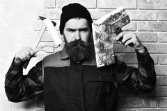 Bearded builder man holding various building tools with serious face. Bearded builder man, long beard, brutal caucasian hipster with moustache in uniform holding stock photos