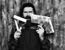 Bearded builder man holding various building tools with surprised face. Bearded builder man, long beard, brutal caucasian hipster with moustache in uniform stock photography