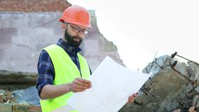 Bearded building engineer in orange helmet on destroyed building background. Serious builder analysing drawing stock footage