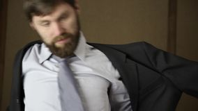 Bearded business executive man wears a jacket, yawning and shaking from a cold on a next day after a party.  stock video