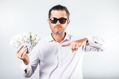 Bearded business man in shirt holding money and looking at the c stock image