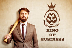 Bearded businessman with baseball bat near lion sketch. Close up of bearded businessman holding baseball bat and standing near concrete wall with king of Stock Photo