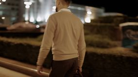 A bearded businessman in a beige jacket with a bag in his hand walks through the night city. The sidewalk across the avenue past the buildings. Back view. Slow stock footage