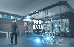 Bearded businessman, big data hologram, office. Rear view of a bearded young businessman in a dark suit looking at a big data hologram in a brick office. Toned Stock Photo
