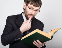 Bearded businessman in a business suit and tie, reading a thick book Stock Photos