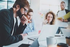 Bearded businessman with business team making conversation at sunny meeting room.Horizontal.Blurred background. royalty free stock photo
