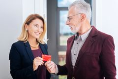 Bearded businessman buying new house giving his credit card to estate agent. Credit card. Bearded businessman wearing dark red jacket buying new house giving his stock images