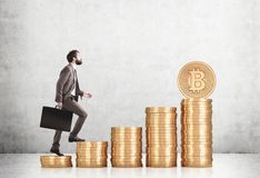 Bearded businessman climbing stacks of bitcoins. Side view of a bearded businessman in a brown suit climbing stacks of bitcoins in a concrete room. Mock up Stock Photos