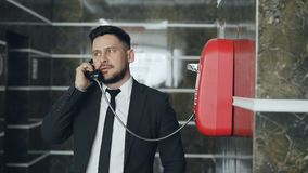 Bearded businessman dial red telephone talking with staff at reception in hotel lobby. Business, travel and people. Bearded young businessman dial red telephone stock video footage