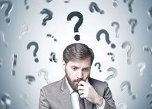 Bearded businessman in doubt, many questions. Young businessman with dark hair and a beard wearing a suit is thinking. A gray wall background with question marks Stock Photo