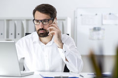 Bearded businessman in glasses on the phone Royalty Free Stock Photo