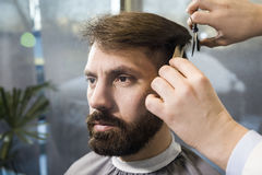 Bearded businessman having hair cut royalty free stock photos