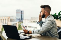 Free Bearded Businessman Hipster Talking On Phone While Sitting At Desk In Office,holds Document,sad Looking At Window. Royalty Free Stock Image - 128706376