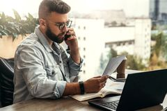 Bearded businessman hipster talking on phone while sitting at desk in office, sad looking at documents. Fall in profits. stock image