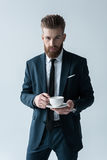 Bearded businessman holding coffee cup and looking at camera. Stylish bearded businessman holding coffee cup and looking at camera Royalty Free Stock Photos