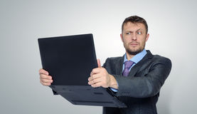 Bearded businessman holding a laptop. On background Royalty Free Stock Photography