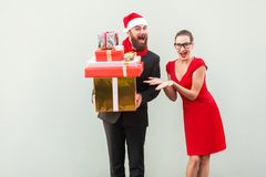 Bearded businessman holding many gift box, woman shows his hands. Bearded businessman holding many gift box, women shows his hands on box. Happiness and funny stock photos