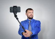 Bearded Businessman making selfie with a stick Stock Photography