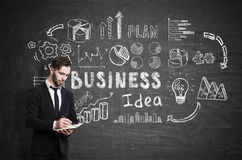 Bearded businessman with a notebook is writing while standing near a blackboard Royalty Free Stock Image