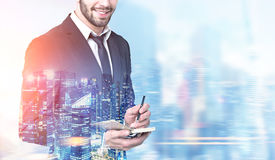 Bearded businessman with a planner in a blue city. Close up of an unrecognizable bearded young businessman taking notes in his planner while standing against a Royalty Free Stock Image