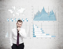 Bearded businessman in red tie and blue and white graphs on conc Royalty Free Stock Images