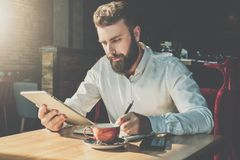 Bearded businessman sits in cafe at table,uses tablet computer and writes in notebook.Man is working Stock Photos