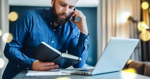 Bearded businessman sitting in front of computer, talking on cell phone while looking in notebook. Freelancer works home. Young bearded businessman is sitting in Royalty Free Stock Photos