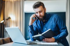 Bearded businessman sitting in front of computer, talking on cell phone while looking in notebook. Freelancer works home. Young bearded businessman is sitting in Royalty Free Stock Images