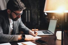Bearded businessman sitting in night loft office and working with documents and contemporary laptop. Stylish man with glasses sits. By the wooden table with stock photos