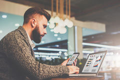 Bearded businessman sitting at table in cafe,holding smartphone and using laptop with charts,graphs on screen. Side view.Young bearded businessman sitting at stock photography