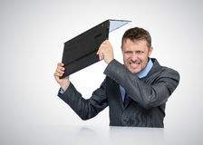 Bearded Businessman smashing his laptop Stock Image