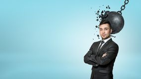 A bearded businessman stands with folded arms while a wrecking ball connects with his head. Stock Image