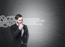 Bearded businessman in a suit is standing near a blackboard with tangled arrows sketch going straight. Stock Photos