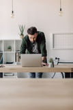 Bearded businessman using laptop in modern office. Concentrated bearded businessman using laptop in modern office Royalty Free Stock Photography