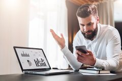 Bearded businessman in white shirt is sitting at table in front of laptop with graphs, charts, diagrams on screen. Young bearded businessman in white shirt is royalty free stock image