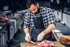 Bearded butcher cut fresh bacon meat. Bearded butcher dressed in a fleece shirt cut fresh bacon meat royalty free stock photo