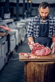 Bearded butcher cut fresh bacon meat. Bearded butcher dressed in a fleece shirt cut fresh bacon meat stock image