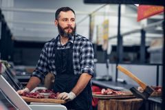 Bearded butcher serving fresh cut meat. Bearded butcher dressed in a fleece shirt serving fresh cut meat in a market stock photography