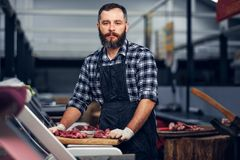 Bearded butcher serving fresh cut meat. Bearded butcher dressed in a fleece shirt serving fresh cut meat in a market stock photo