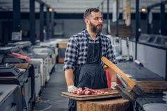 Bearded butcher serving fresh cut meat. Bearded butcher dressed in a fleece shirt serving fresh cut meat in a market stock image