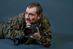 Bearded camera man. Bearded camera man dressed in camouflage uniform lying on the floor hunts his target with camera in his hands Royalty Free Stock Photography