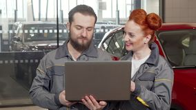 Bearded car mechanic using laptop at the garage, working with female colleague. Lovely red haired female auto technician enjoying working at the service stock video footage