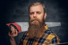 A bearded carpenter man dressed in a plaid shirt holds handsaw. Royalty Free Stock Photography