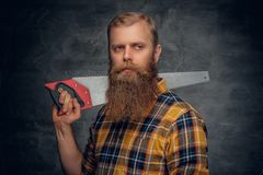 A bearded carpenter man dressed in a plaid shirt holds handsaw. Stock Photos