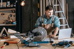 Bearded carpenter planning woodworking project stock photography