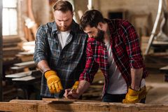 bearded carpenter in protective gloves pointing on wooden plank to partner with pen royalty free stock image