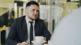 Bearded Caucasian businessman gesticulating and discussing his startup plan with investor in formal wear in glassy cafe. Bearded Caucasian entrepreneur stock video footage