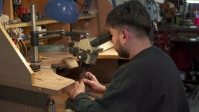 Jeweler creates new jewelry. Bearded caucasian jeweler creating new jewelry. Young man using microscope to have a better view of working process. Professional Stock Photos